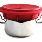 Norpro red silicone food steamer insert sitting on pot